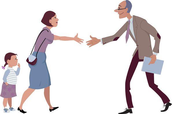 Gute Zusammenarbeit mit Eltern: Lehrer begrüßt eine Mutter zu einem kurzen Gespräch