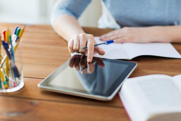 Lehrkraft arbeitet mit einem Tablet. Es sollte eine eigene Affinität zu digitalen Geräten vorhanden sein, um eine Tabletklasse zu leiten.