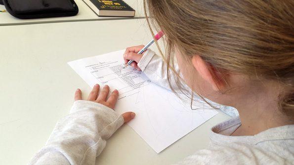 Schülerin füllt ein Kriterienkärtchen aus, mithilfe dessen konstruktive Kritik geübt werden kann.
