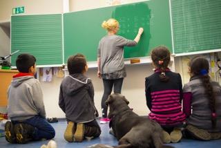 Muslimische Kinder sitzen mit dem Schulhund zusammen