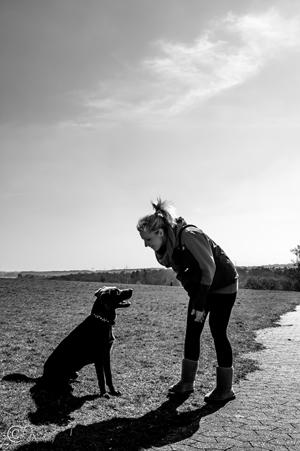 Frau und Hund beim Gassi gehen auf einem Feld.