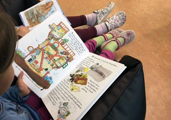Kinder sitzen auf einem Sessel und lesen aus einem Buch dem Schulhund vor.