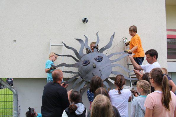 Am Schulgebäude wird die Sonne befestigt, die die Kinder in der Kunstschmiede erstellt haben. So machen außerschulische Lernorte Spaß.