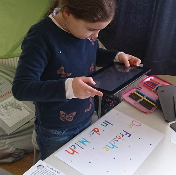 Eine Schülerin aus der Tabletklasse fotografiert mithilfe der Tabletkamera ein selbstgebasteltes Poster.