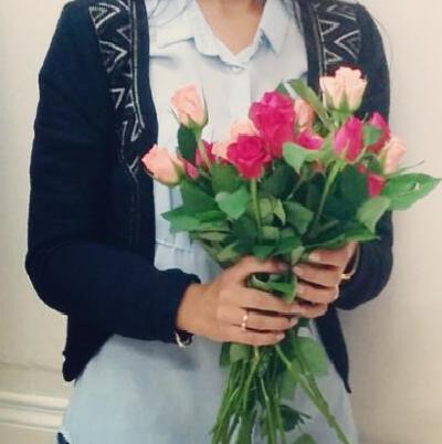 Frisch gebackene Lehrerin am Tag der Prüfung mit einem Strauß Rosen in der Hand.