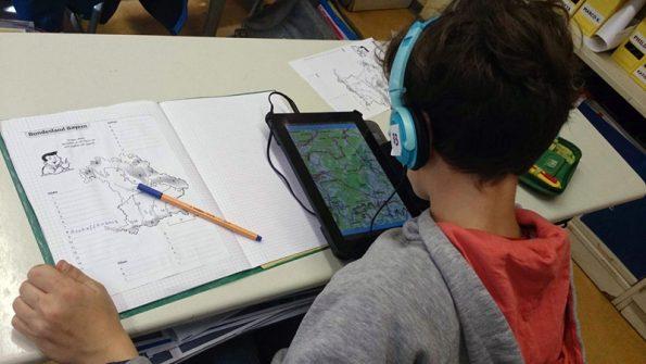 Kind aus der Tabletklasse füllt im Rahmen des Erdkundeunterrichts mithilfe eines Tablets ein Arbeitsblatt aus.