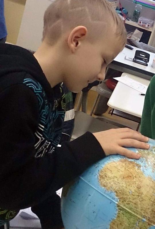 Kind aus der Tabletklasse betrachtet im Rahmen des Erdkundeunterrichts einen Globus.