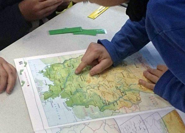 Kind aus der Tabletklasse liest im Rahmen des Erdkundeunterrichts eine Deutschlandkarte.