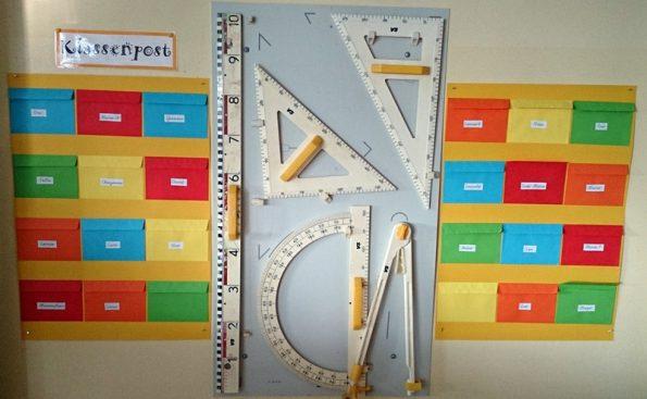 Lineale und bunte Umschläge für die Klassenpost hängen unter der Tafel.