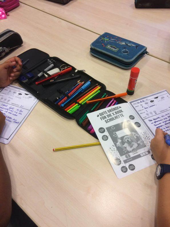 Kinder schreiben in ein kleines Heft, das als Reisetagebuch geführt wird.