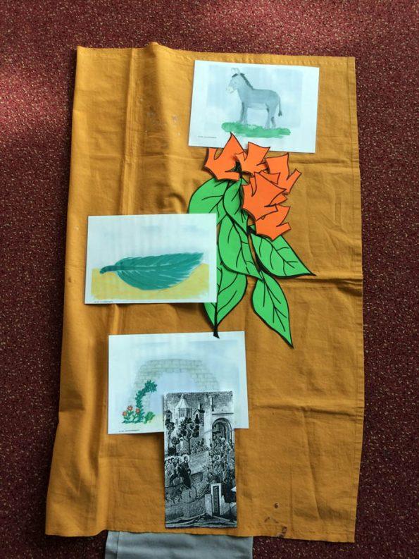 Bodenbild mit einem Tuch und darauf abgelegten Symbolen zum Thema Ostern.