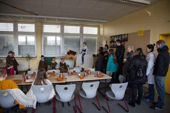 Kinder führen im Klassenraum ein Theaterstück auf, die Eltern schauen zu.