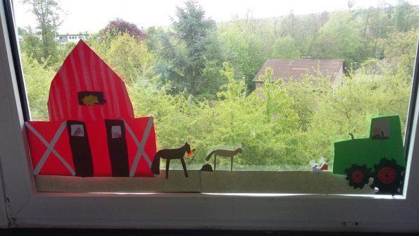 Fensterbilder kann man thematisch gestalten lassen. Hier zu sehen sind ein Traktor, eine Scheune sowie Tiere zum Thema Bauernhof.