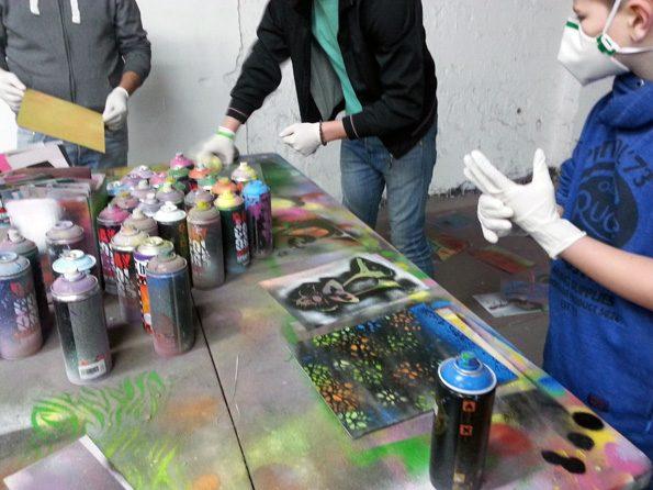 Kinder stehen um einen Tisch und fertigen eigene Graffities während der Klassenfahrt an.