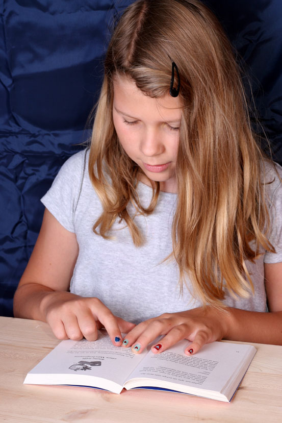 Mädchen liest ein Buch und bereitet sich auf den Vorlesewettbewerb vor.