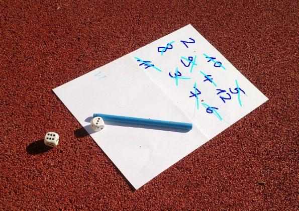 Zettel, zwei Würfel und ein Stift liegen auf dem Boden der Sporthalle und dienen dem Training der Ausdauer.