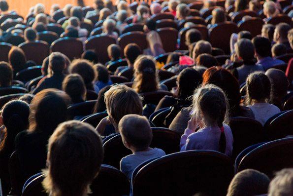 Ein Ausflug ins Theater begeistert die Schülerinnen und Schüler. Ein Blick in den Zuschauerraum des Theaters zeigt die Spannung.