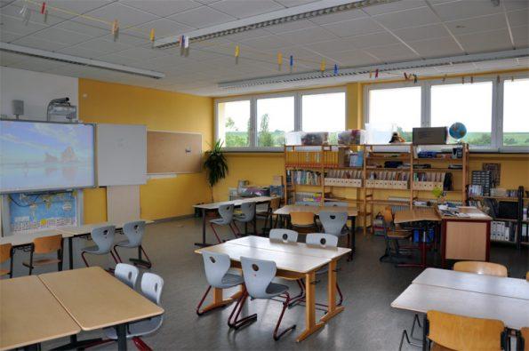 Klassenraum mit mehreren Schülergruppentischen und einem Lehrertisch, der einem Schülertisch gegenüber steht. Eine etwas andere Sitzordnung.