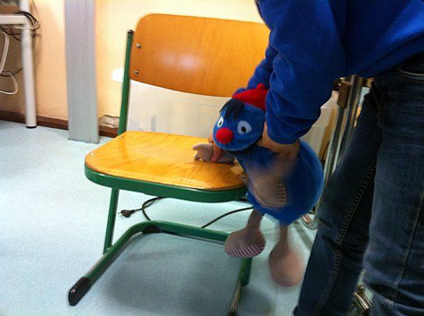 """Kind spielt mit Klassentier Max in der DaZ-Sprachfördergruppe das Spiel """"Mein rechter rechter Platz ist frei""""."""