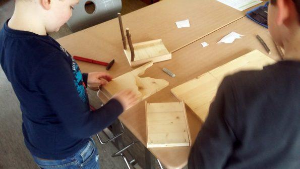 Junge steht mit einem Mitschüler am Tisch und misst das Holz für den Bau der Futterhäuschen.