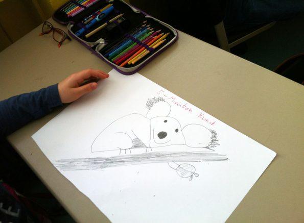 Auf dem Schultisch liegt ein Zeichenblatt, auf dem ein Koalabär abgebildet ist. Ein Kind hat den Koala aus einem vorgezeichneten Y gemalt.