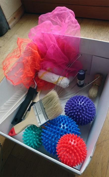 Box mit Massagebällen, Pinseln, Malerrollen usw., die die Kinder für Massagen zur Entspannung verwenden können.