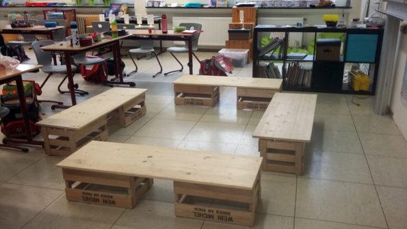 Sitzbänke aus Leimholz und Weinkisten, die im Klassenraum im Kreis aufgestellt sind.