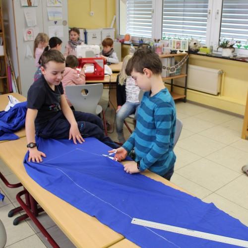 Kinder schneiden in einem Klassenzimmer im Rahmen der Projektwoche ein Stück Stoff.