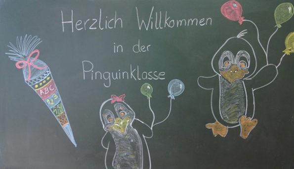 Das Klassenmaskottchen Pinguin empfängt die Schulkinder an der Tafel im Klassenraum.